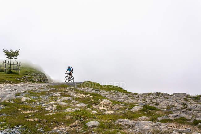 Motociclista da montanha andando em pista de terra — Fotografia de Stock