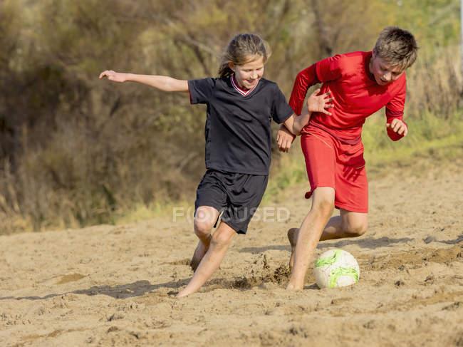 Дівчинка і хлопчик грали у футбол — стокове фото
