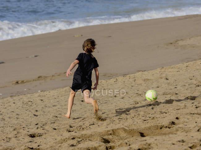 Девушка гоняется за футбольным мячом по песку — стоковое фото