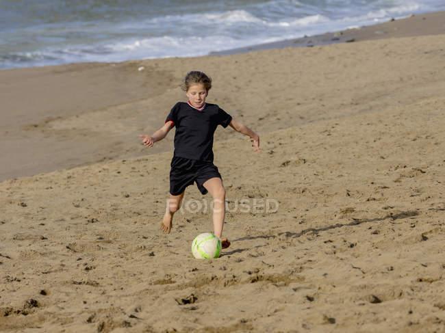 Дівчина переслідують футбольний м'яч через пісок — стокове фото