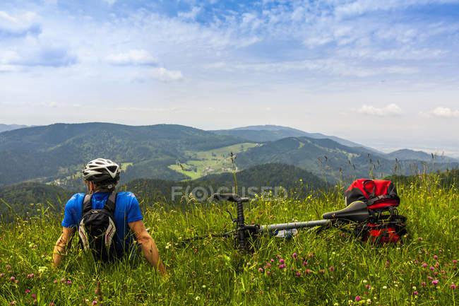 Homem relaxando na grama e olhar para as montanhas — Fotografia de Stock
