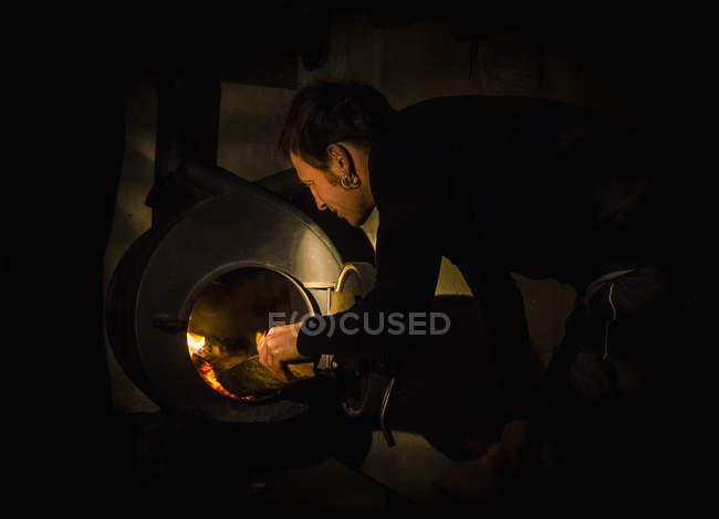 Человек кладет дрова в духовку — стоковое фото