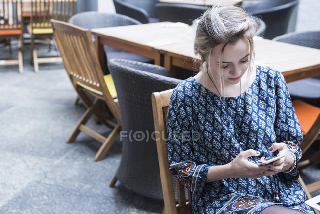 Woman text messaging at restaurant — Stock Photo