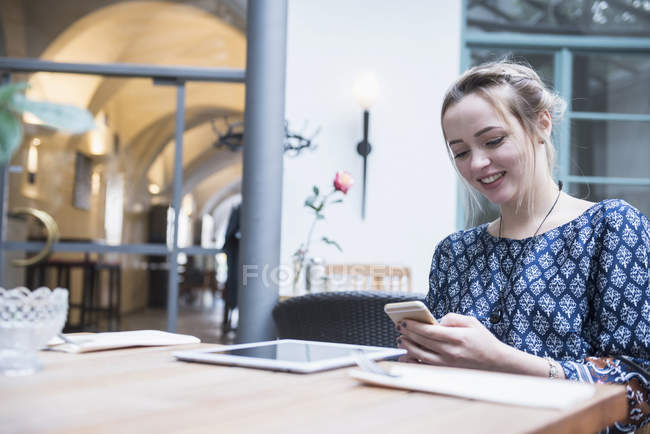 Woman messaging on mobile at restaurant — Stock Photo
