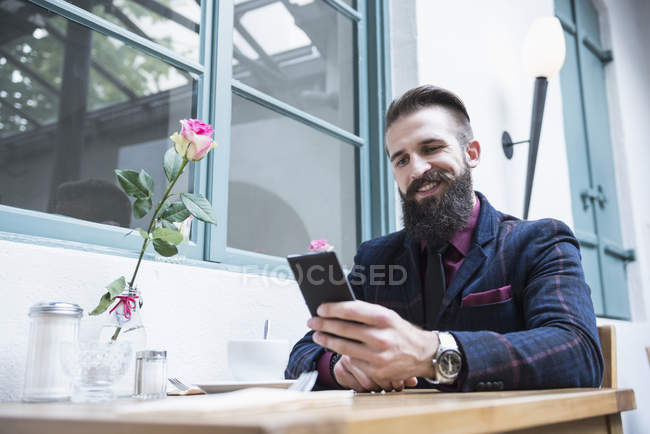 Man smiling while using cell phone — Stock Photo