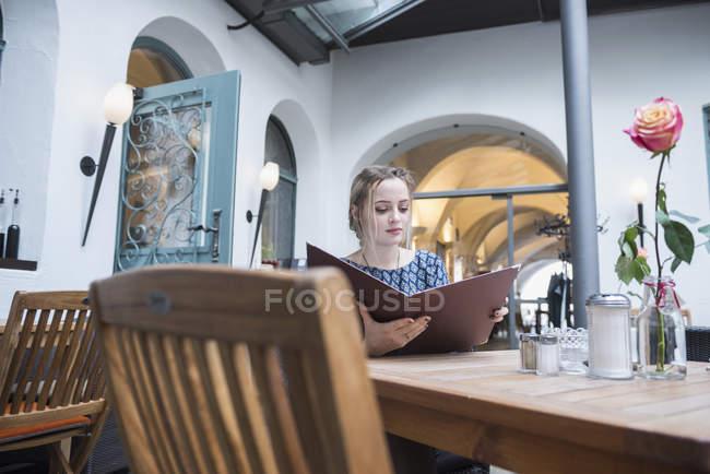 Mujer que sostiene la carta en el restaurante - foto de stock
