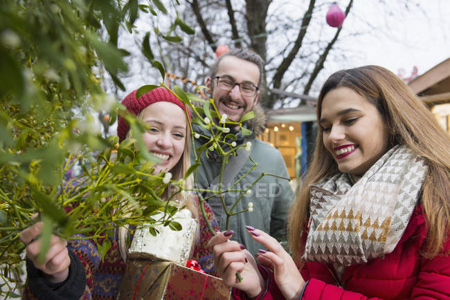 Friends with gifts and mistletoe twigs — Stock Photo