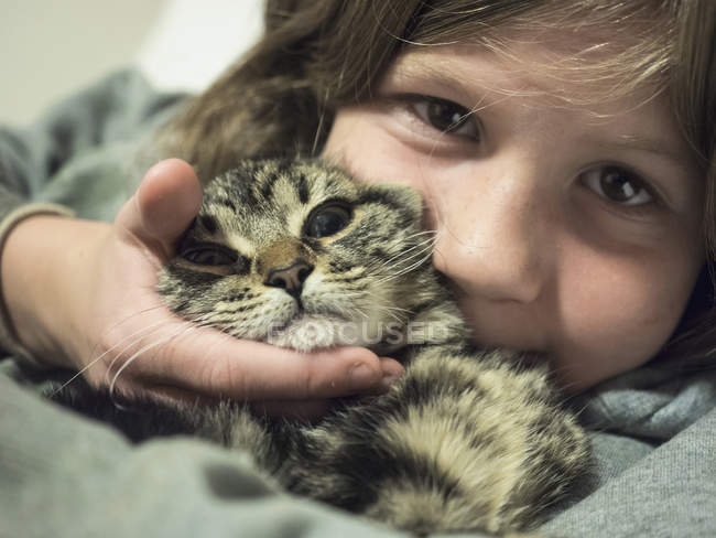 Close-up portrait of girl cuddling with cat — Stock Photo