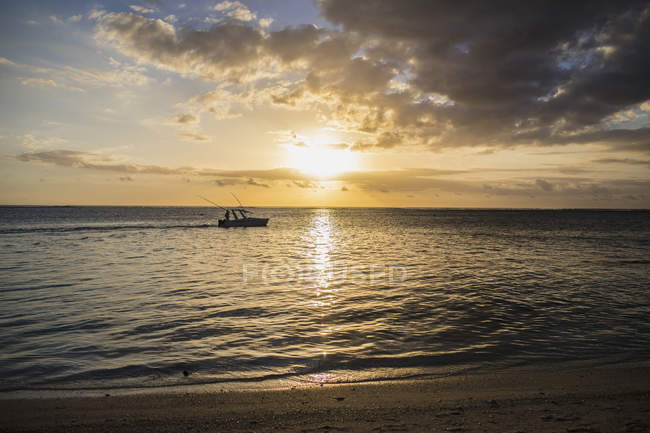 Fishing boat on sea at sunset — Stock Photo