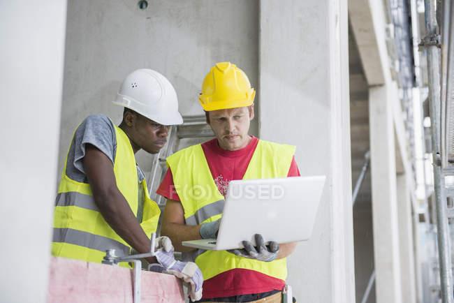 Будівельних робітників, використовуючи ноутбук в будівлі сайту — стокове фото