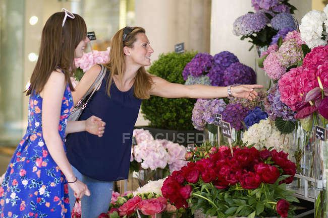 Two women choosing flowers at market stall — Stock Photo