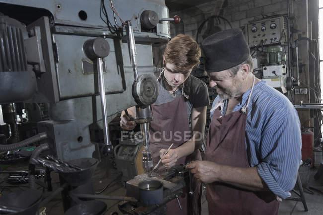 Кузнец объясняя ученик обработки сверлильный станок — стоковое фото