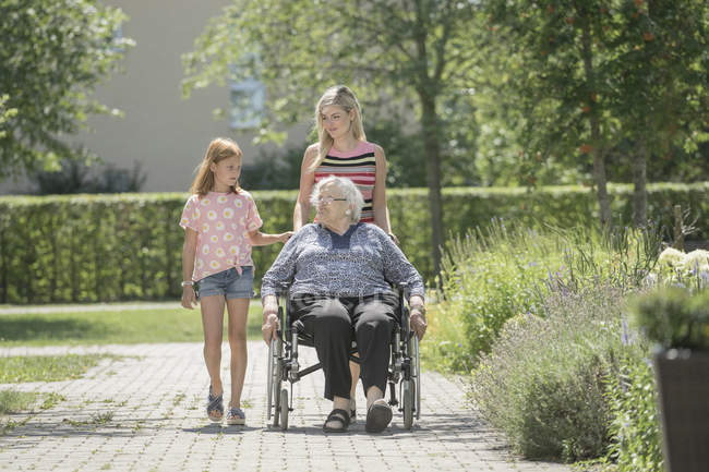 Senior woman on wheelchair with granddaughters at rest home park — Stock Photo