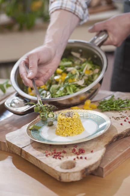 Close-up de mãos masculinas servindo o prato de arroz com legumes — Fotografia de Stock