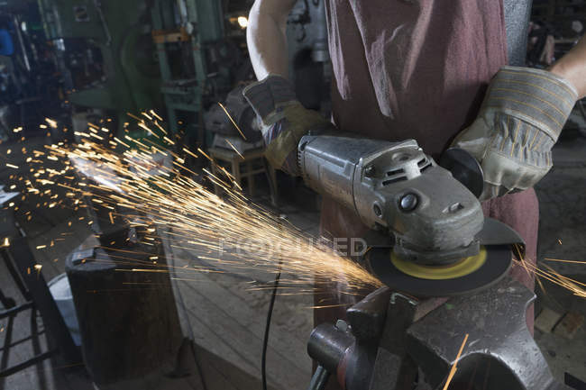 Trainee blacksmith cutting iron bar with angle grinder at workshop — Stock Photo
