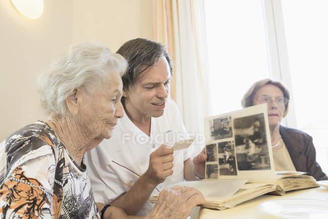Zelador assistindo álbum de fotos com mulheres idosas em casa de repouso — Fotografia de Stock