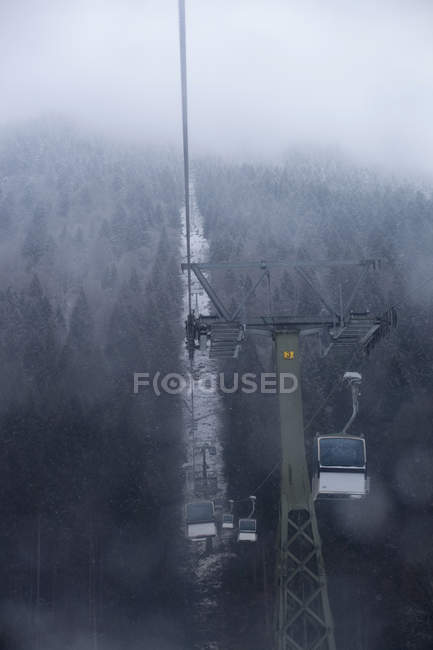 Overhead view of cable cars above snow covered trees in forest — Stock Photo