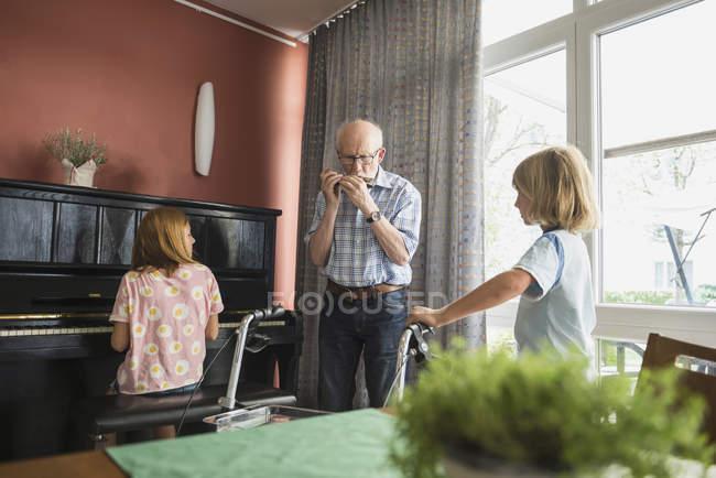 Nonno che gioca strumento armonica con i bambini — Foto stock
