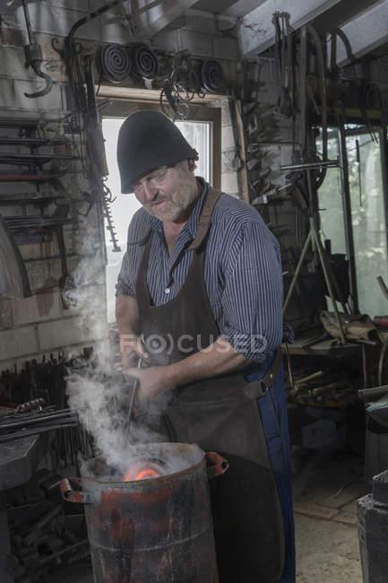 Blacksmith cooling down hot iron bar at workshop — Stock Photo