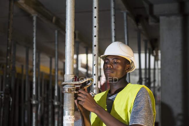 Construction worker fixing pillar in basement of building site — Stock Photo