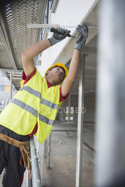 Construction worker with hammer at building site verifying dimensions — Stock Photo