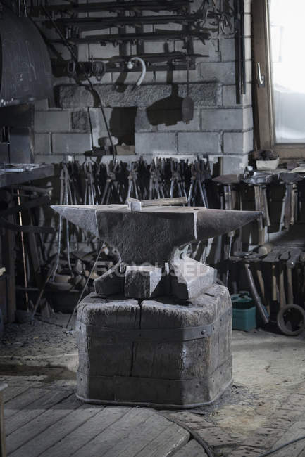 Hammer lying on iron anvil in traditional blacksmith forge — Stock Photo