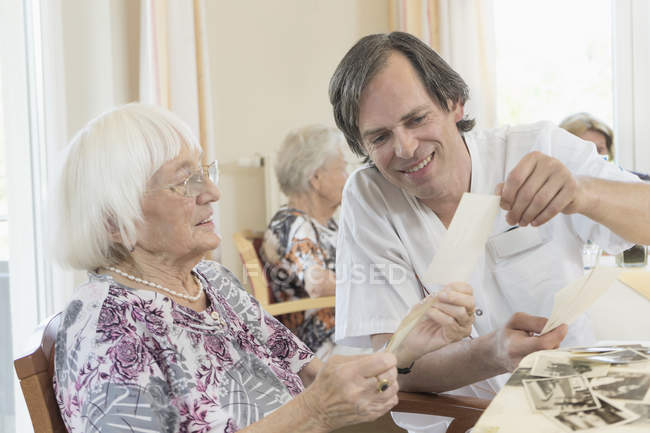 Caretaker watching photos with senior women at rest home — Stock Photo