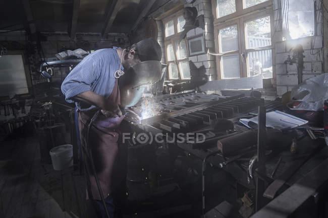 Кузнец, фьюзинг садовые ворота в мастерской — стоковое фото