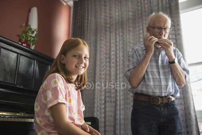 Nipote di ascolto mentre nonno suonare armonica strumento — Foto stock