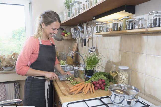 Frau schneiden Spargel in Küche — Stockfoto