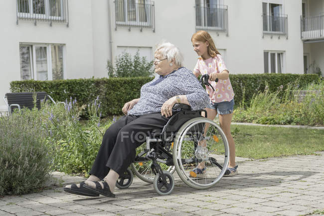 Senior woman on wheelchair with granddaughter at rest home park — Stock Photo