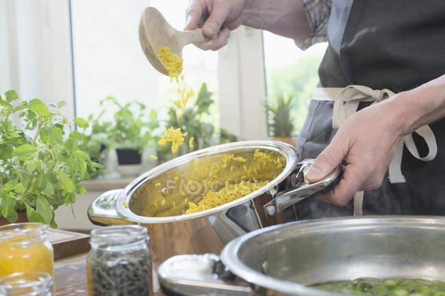 Close-up do homem mexendo o arroz com a colher de pau na panela — Fotografia de Stock
