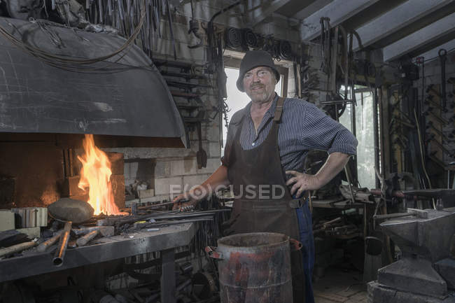 Blacksmith heating iron bar in forge at workshop — Stock Photo