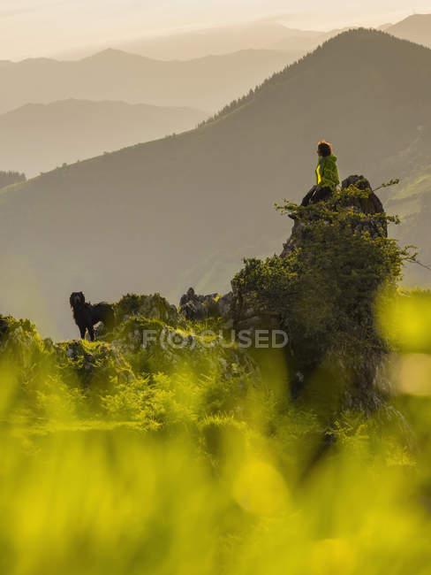 Mujer con perro de excursión a la montaña Ganekogorta - foto de stock