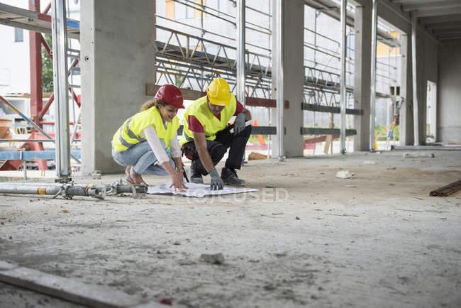 Будівельники рецензування blueprint в будівлі сайту — стокове фото