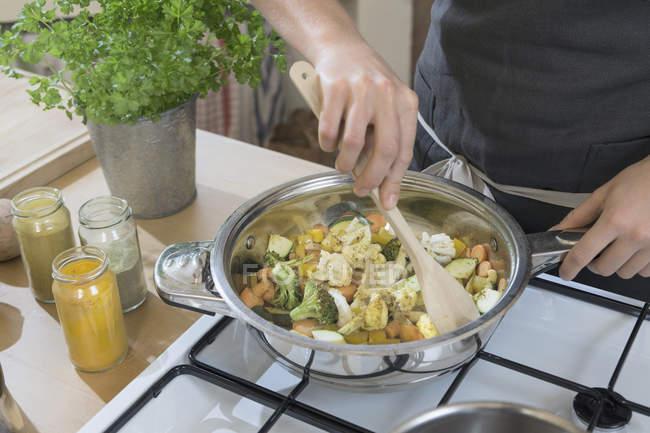 Close-up da mulher mexendo legumes com colher em panela — Fotografia de Stock