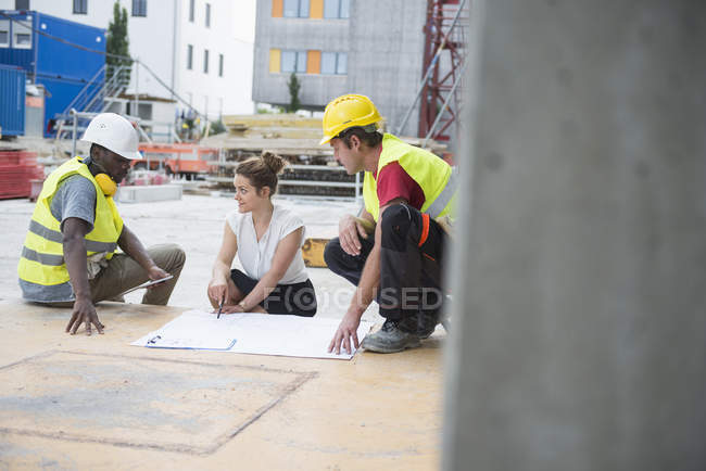 Architect reviewing blueprint with construction workers at building site — Stock Photo