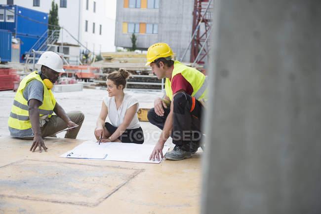 Архітектор рецензування blueprint з будівельних робітників на будівлі сайту — стокове фото
