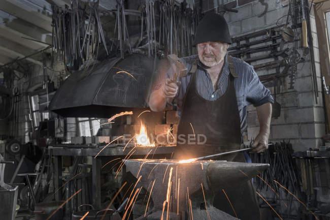 Blacksmith hammering hot iron bar on anvil at workshop — Stock Photo