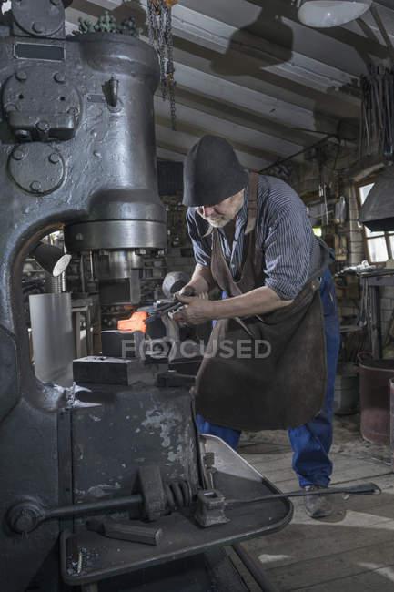 Schmied Hämmern rote heiße Eisenstange in Hammer-Maschine beim workshop — Stockfoto