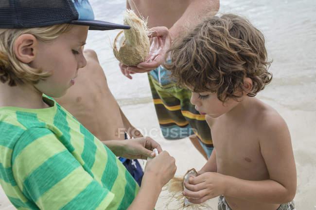 Children sharing coconut at beach — Stock Photo