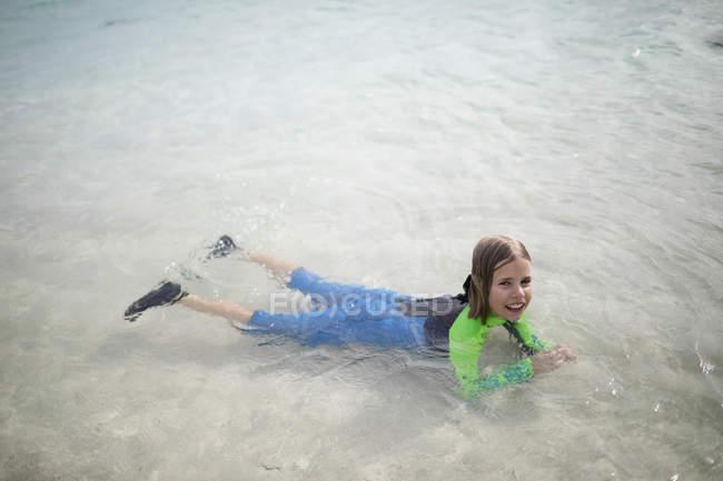 Menina no wetsuit flutuando na água — Fotografia de Stock