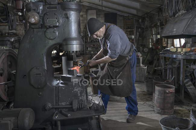 Кузнец стучащий красный горячий утюг бар в молот машины на семинаре — стоковое фото