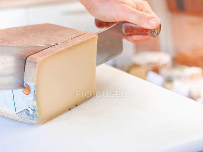Vista de primer plano de corte de la mano femenina francesa queso comte - foto de stock