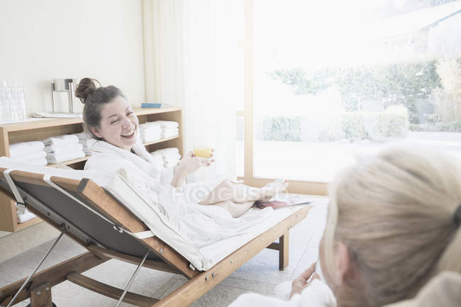 edba226438 Women in bathrobes relaxing at spa with fresh juice — Stock Photo