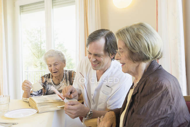 Caretaker watching photo album with senior women at rest home — Stock Photo