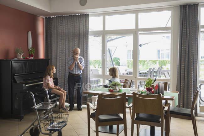 Nipoti ascolto mentre nonno suonare armonica strumento — Foto stock