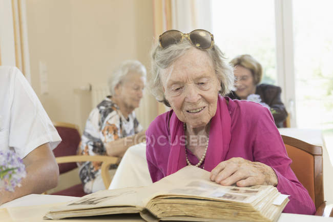 Senior woman watching photo album in rest home — Stock Photo
