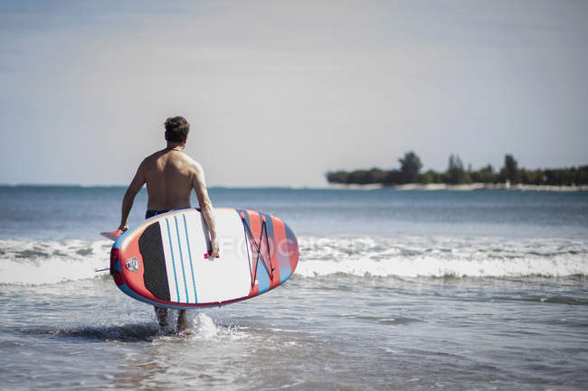 Rear view of man carrying surfboard while walking into sea — Stock Photo