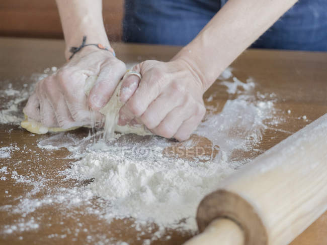 Cropped view of female hands kneading dough on table — Stock Photo